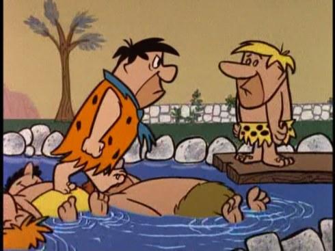 Fred Flintstone standing on people floating in pool, talking to Barney