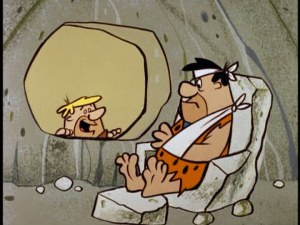 Fred, with bandaged head and arm, talks to Barney through window
