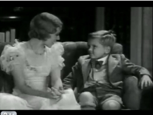 Jackie Cooper sitting on the couch with his teacher, Miss Crabtree. From Love Business